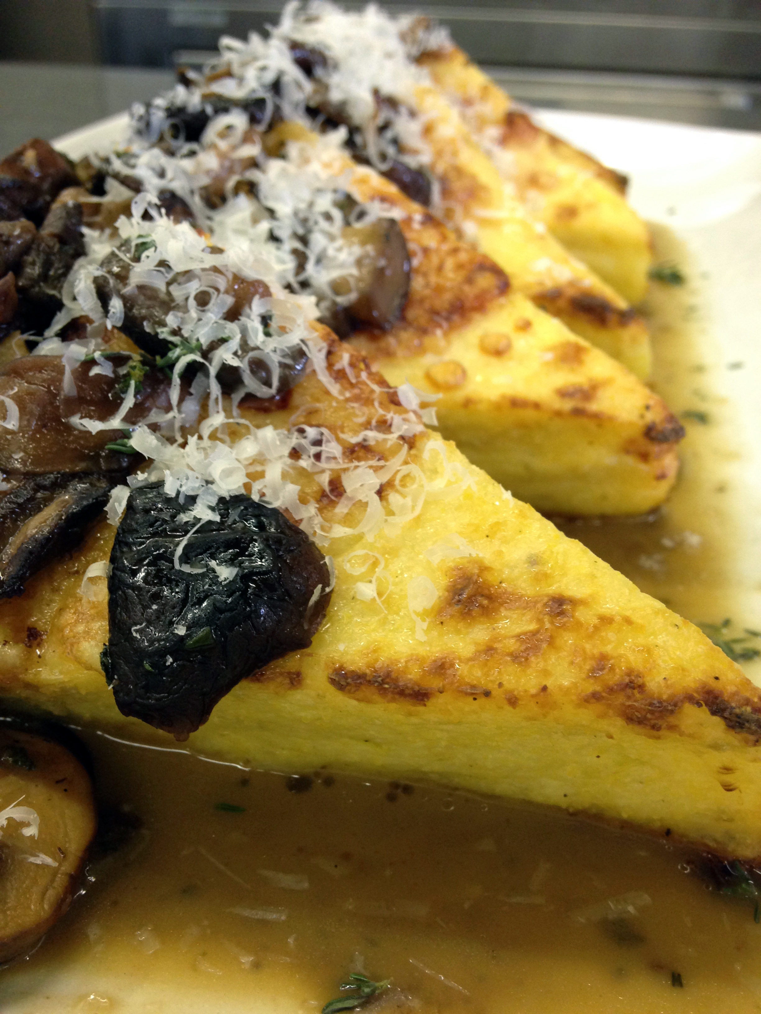 Chef Chris took our cooled polenta, cut it into triangles, topped with butter and Parmesan and baked it until golden. Then he added a savory mushroom sauce.