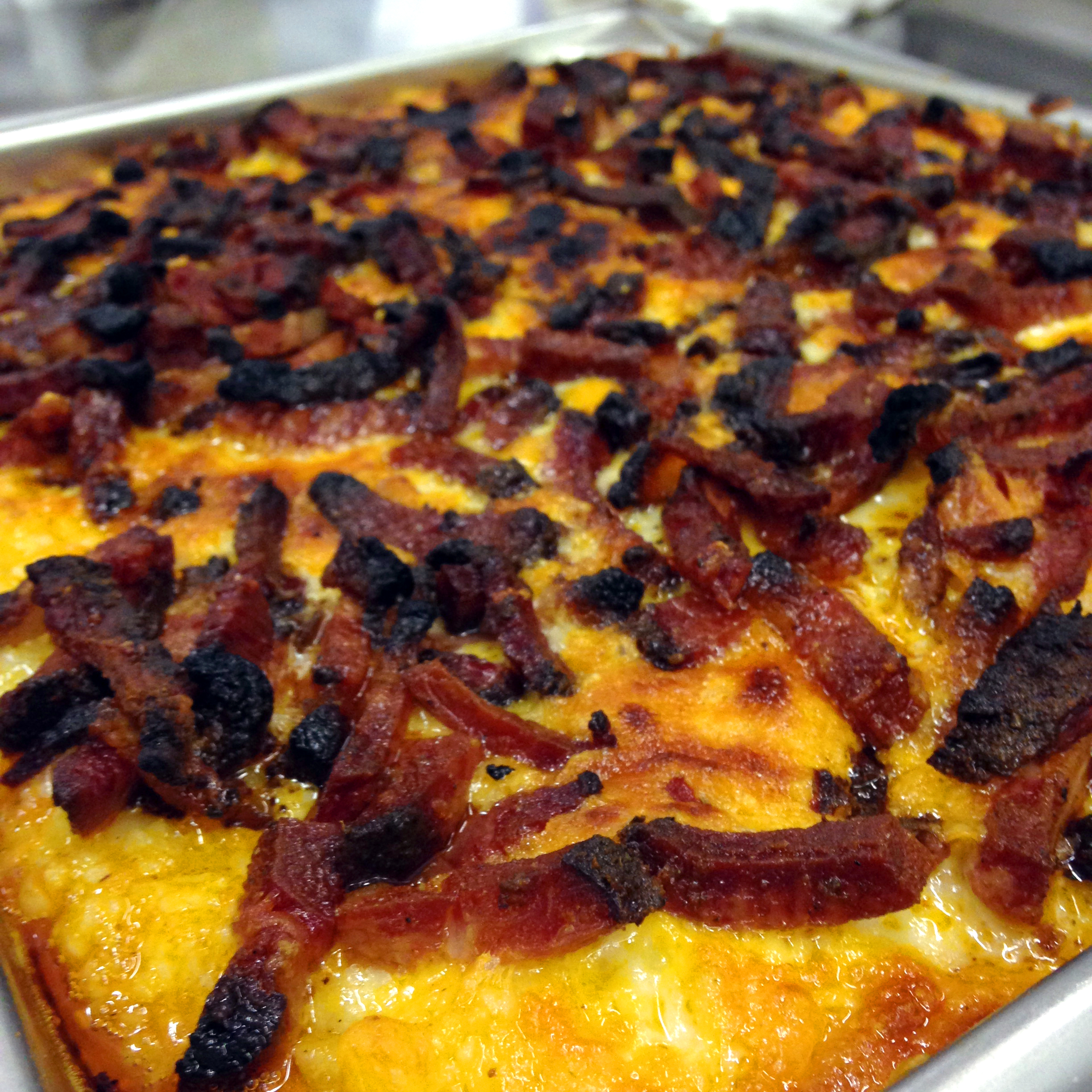 Anson Mills grits were topped with yellow and smoked cheddar, Tasso ham, and broiled 'till bubbly