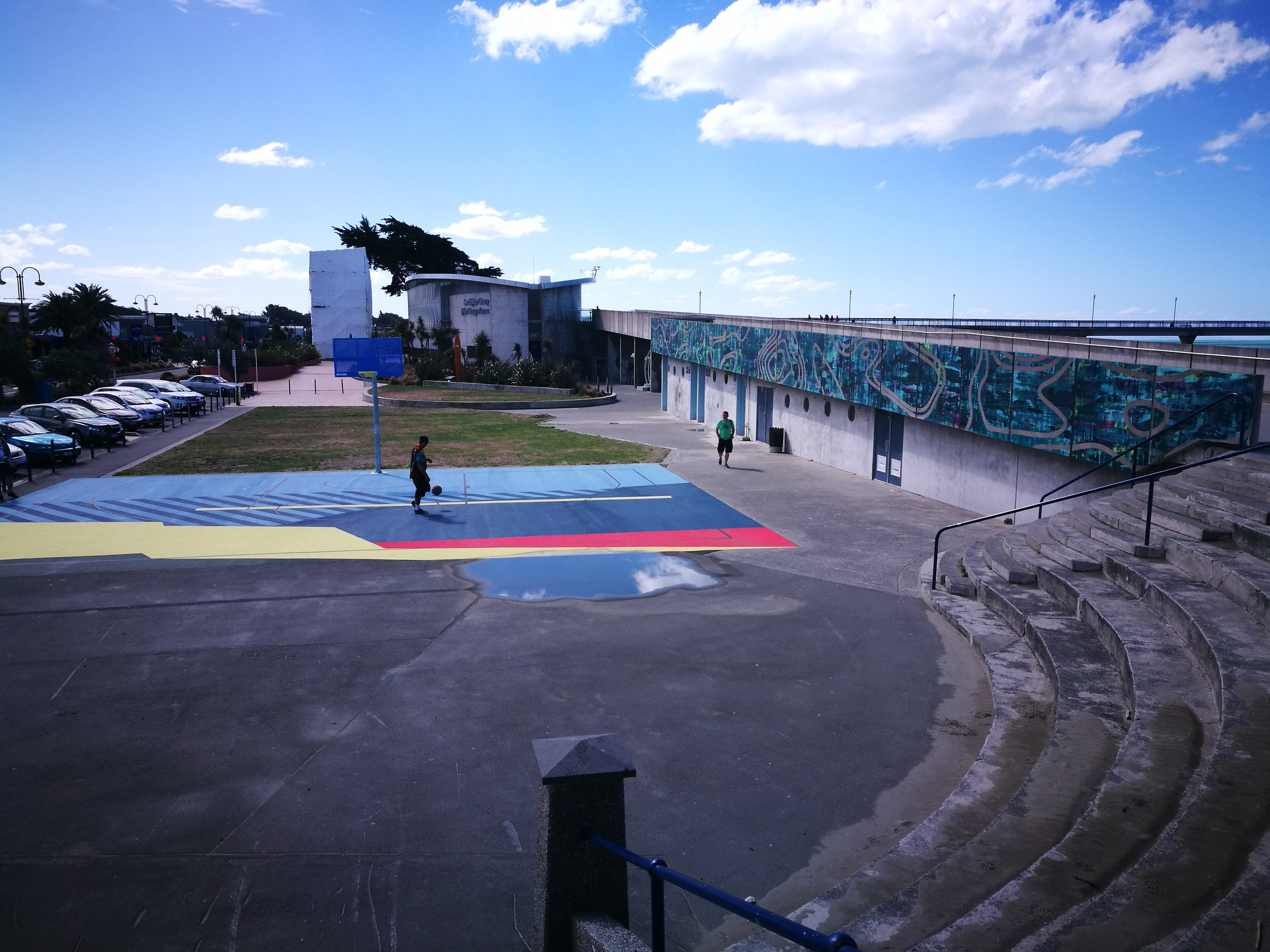 The completed Re:ACTIVATE 2018: New Brighton artworks. Basketball court surface – Nathan Ingram  FORCES  2018. Wall mural – Josh O'Rourke  Low Pressure High Pressure  2018. Image courtesy of the artist and SCAPE Public Art. Photo by Reuben Woods.
