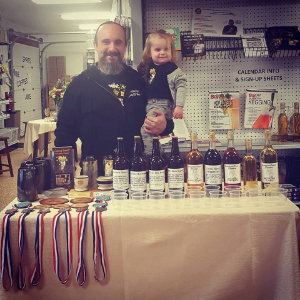 Jon with Pearl and his awards, giving a class about mead