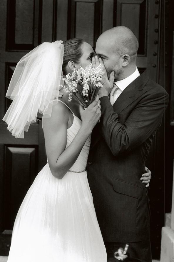 Rosemary Ferguson and Jake Chapman hiding a kiss, Vogue, 2004