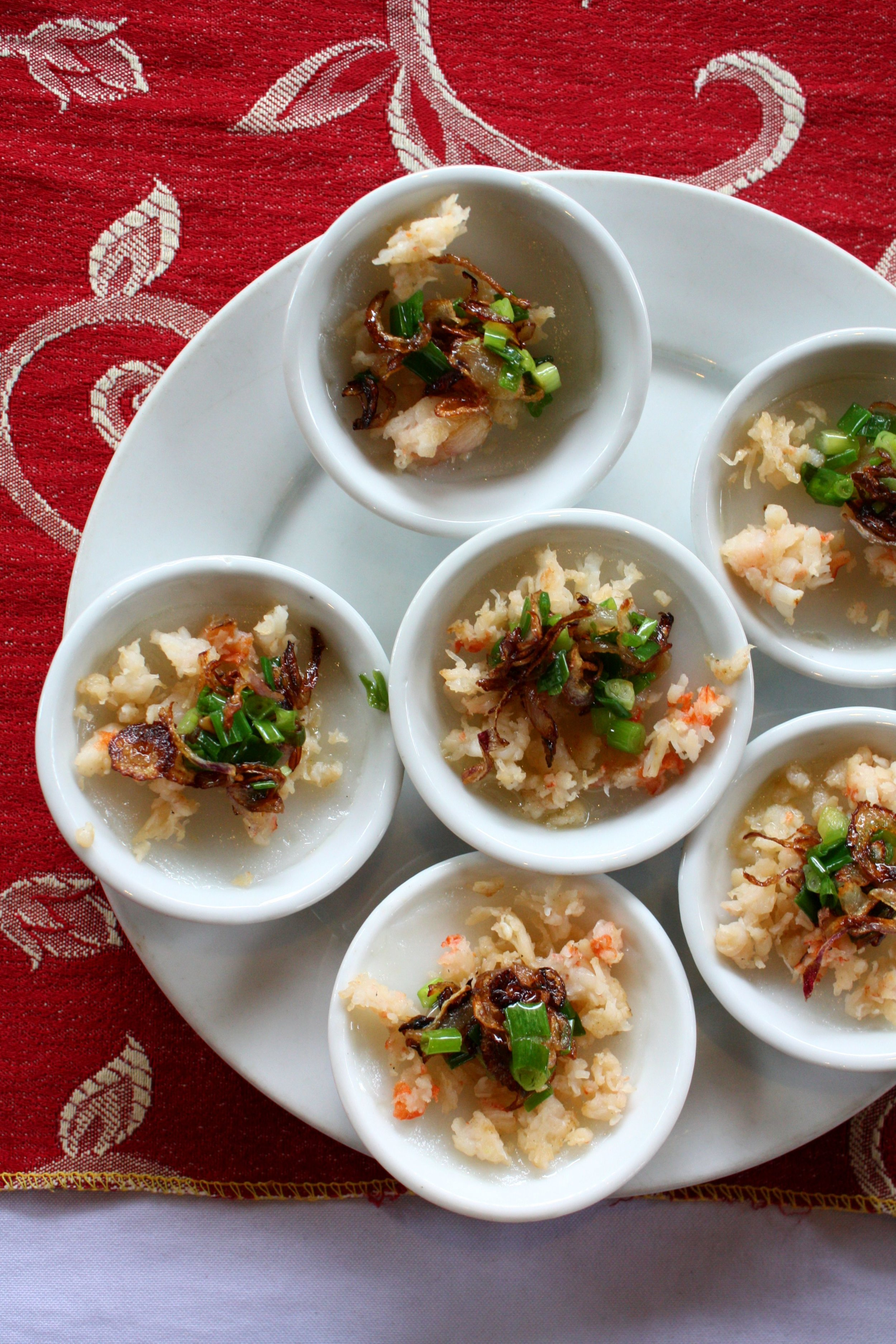 "Freshly steamed Banh Beo (steamed rice flour ""pancakes"") topped with sautéed shrimp, crispy shallots and green onions."