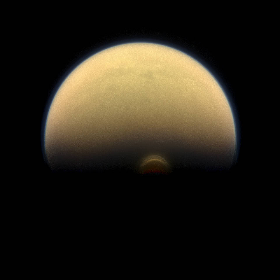 "As winter sets in at Titan's south pole, a cloud system called the south polar vortex (small, bright ""button"") has been forming, as seen in this 2013 image - Image credit: NASA/JPL-Caltech/Space Science Institute"