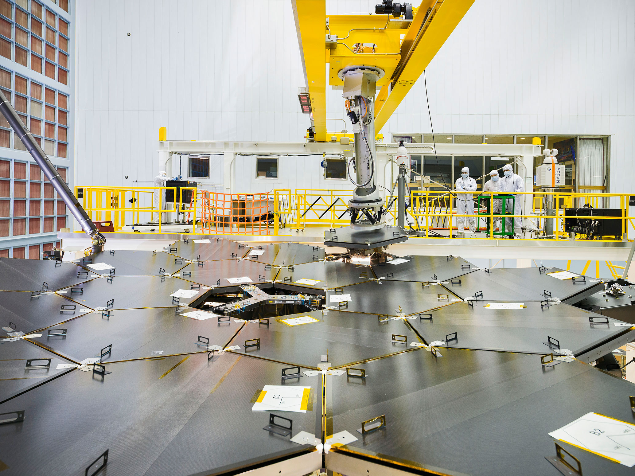 Inside a massive clean room at NASA's Goddard Space Flight Center in Greenbelt, Maryland the James Webb Space Telescope team used a robotic am to install the last of the telescope's 18 mirrors onto the telescope structure. - Image Credits: NASA/Chris Gunn