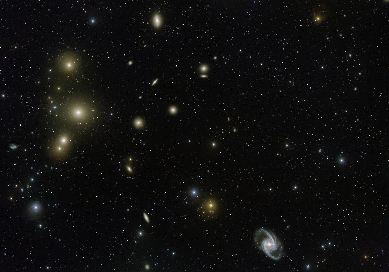 The Fornax Galaxy Cluster is one of the closest of such groupings beyond our Local Group of galaxies. This new VLT Survey Telescope image shows the central part of the cluster in great detail. At the lower-right is the elegant barred-spiral galaxy NGC 1365 and to the left the big elliptical NGC 1399. – Image Credit: ESO. Acknowledgement: Aniello Grado and Luca Limatola