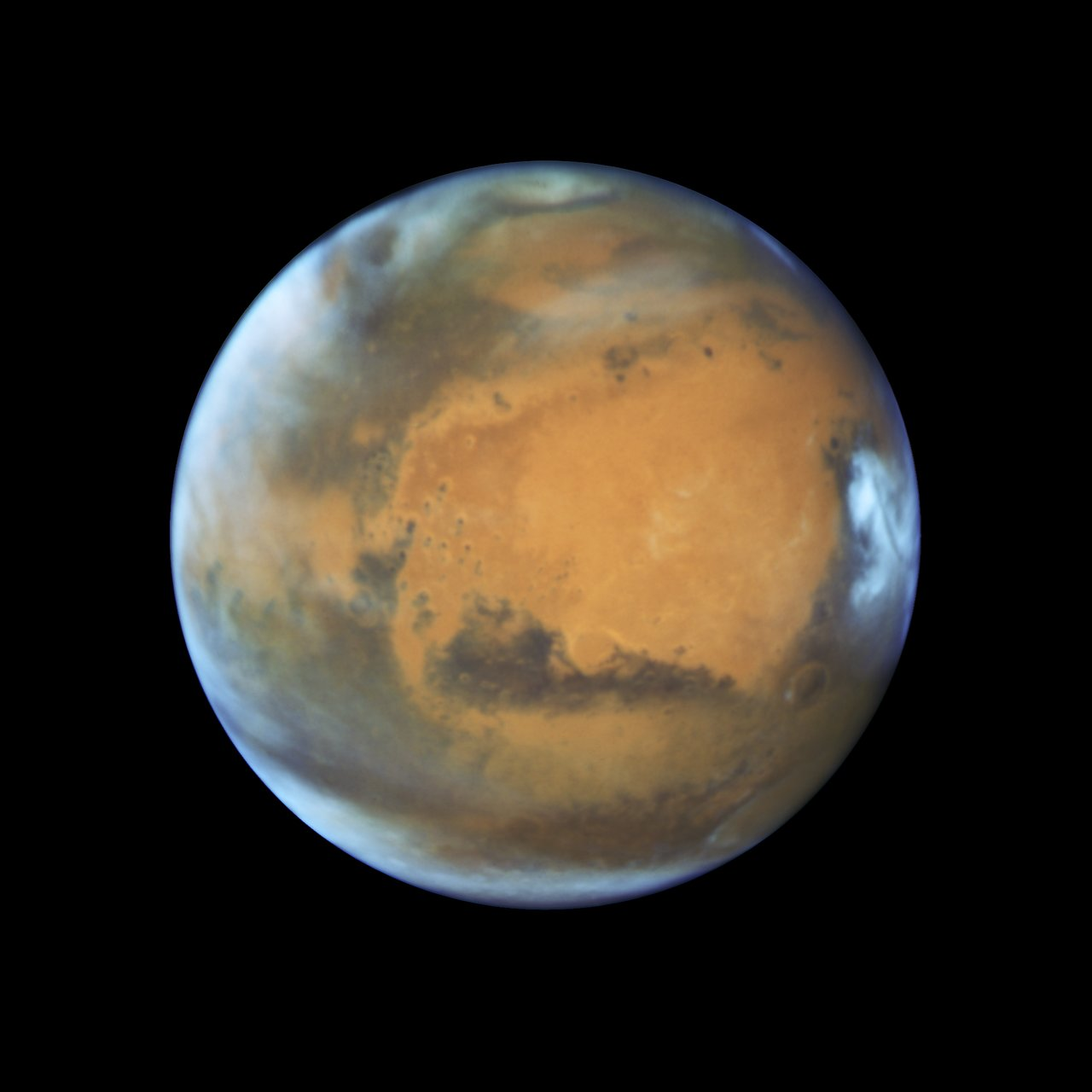 This image shows our neighbouring planet Mars, as it was observed shortly before opposition in 2016 by the NASA/ESA Hubble Space Telescope.  Some prominent features of the planet are clearly visible: the ancient and inactive shield volcano Syrtis Major; the bright and oval Hellas Planitia basin; the heavily eroded Arabia Terra in the centre of the image; the dark features of Sinus Sabaeous and Sinus Meridiani along the equator; and the small southern polar cap. Image   Credit:NASA, ESA, the Hubble Heritage Team (STScI/AURA), J. Bell (ASU), and M. Wolff (Space Science Institute)