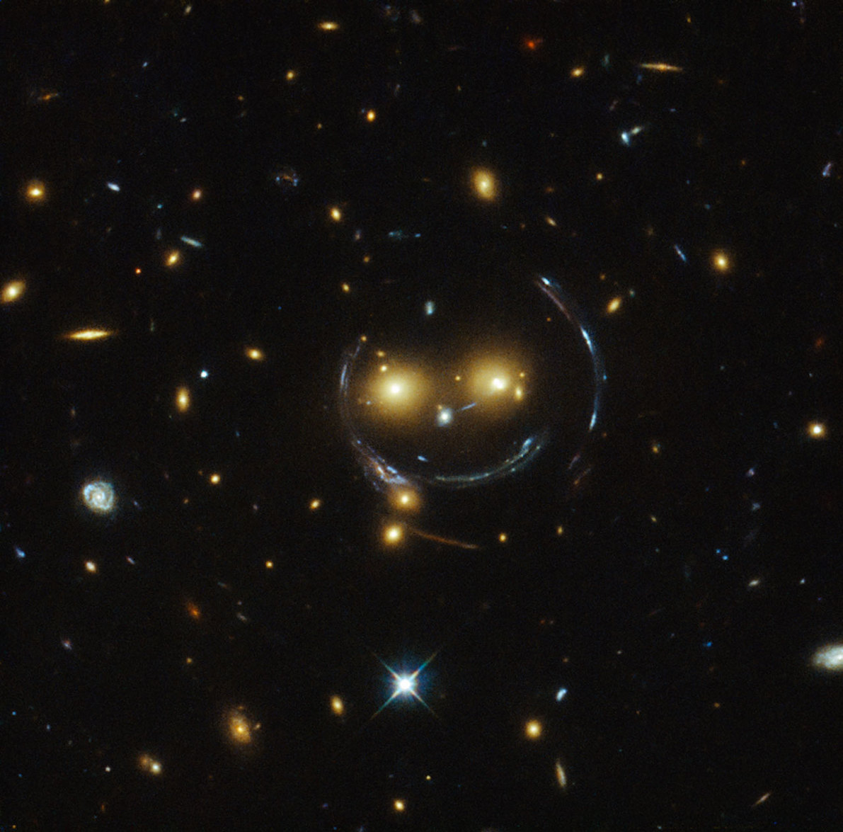 A spectacular smiling gravitational lens, observed by the Hubble Space Telescope. - Image Credit: NASA/ESA