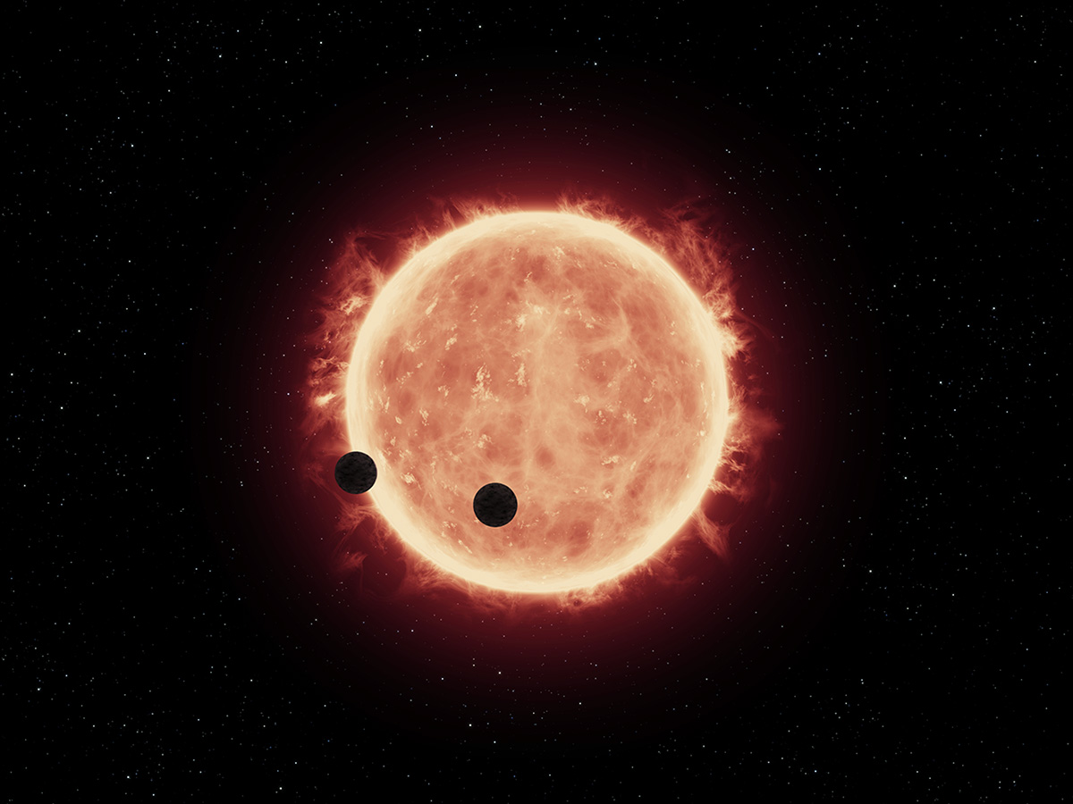 This artist's illustration shows two Earth-sized planets, TRAPPIST-1b and TRAPPIST-1c, passing in front of their parent red dwarf star, which is much smaller and cooler than our sun. NASA's Hubble Space Telescope looked for signs of atmospheres around these planets. – Image Credits: NASA/ESA/STScI/J. de Wit (MIT)