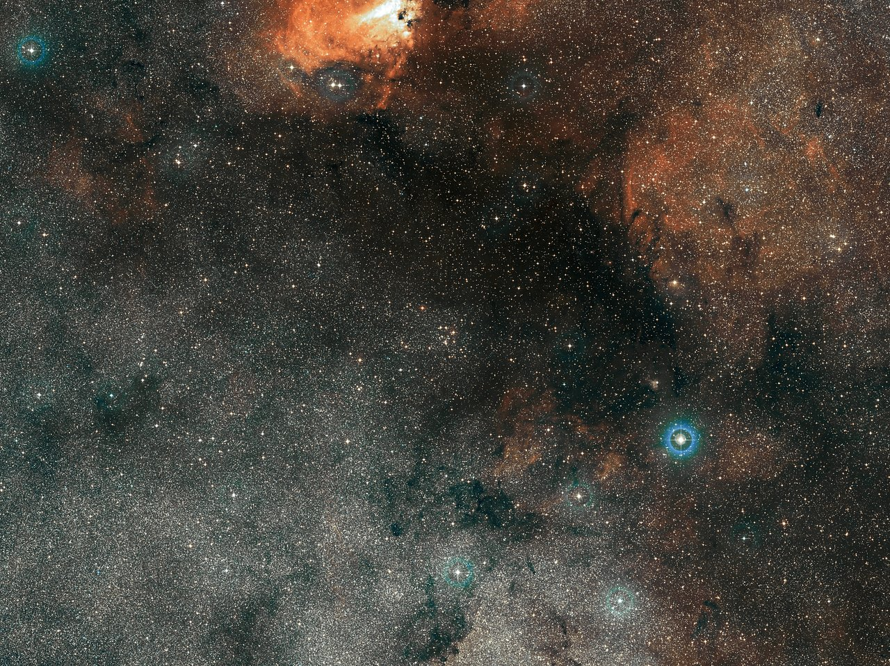 The small smattering of bright stars at the centre of this wide-field view is Messier 18, an open star cluster containing stars that formed together from the same massive cloud of gas and dust. This picture, which also shows part of the bright Omega Nebula (Messier 17) at the top, was created from images forming part of the Digitized Sky Survey 2. - Image Credit:ESO/Digitized Sky Survey 2.   Acknowledgement: Davide De Martin