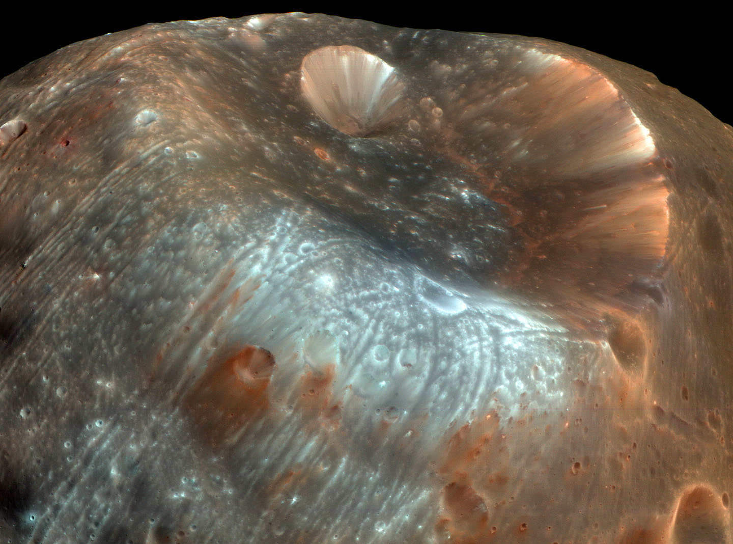 The streaked and stained surface of Phobos, with the Stickney crater shown in the center. - Image Credit: NASA/JPL/Mars Express