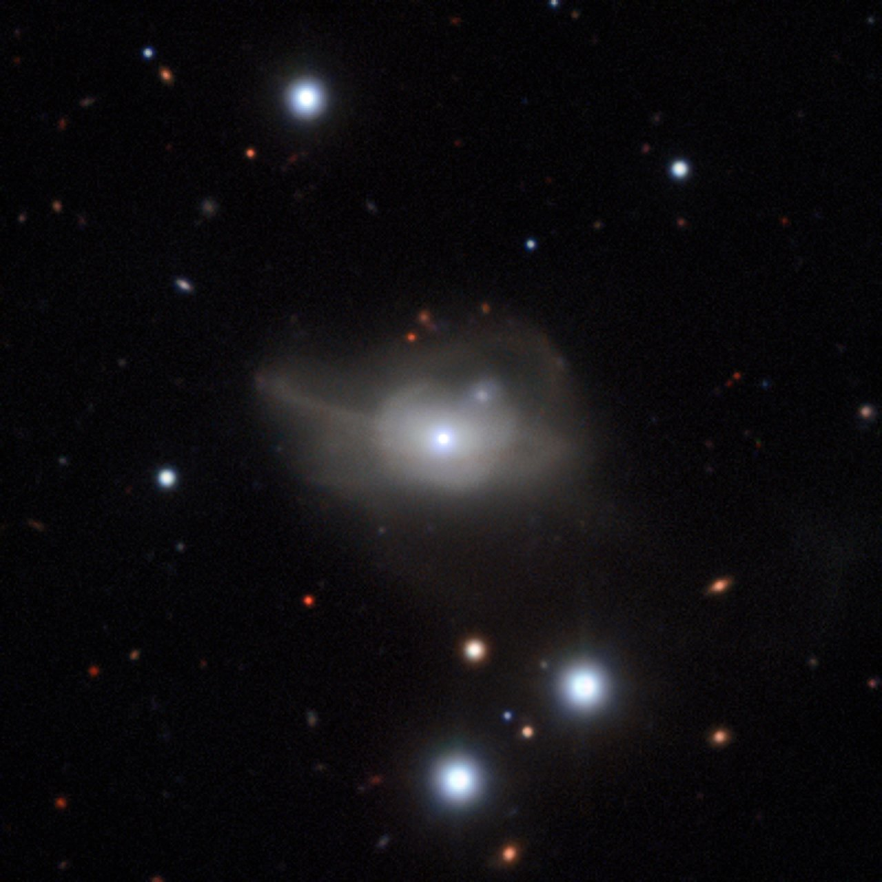 This image from the MUSE instrument on ESO's Very Large Telescope shows the active galaxy Markarian 1018, which has a supermassive black hole at its core. The faint loops of light around the galaxy are a result of its interaction and merger with another galaxy in the recent past. – Image Credit: ESO/CARS survey