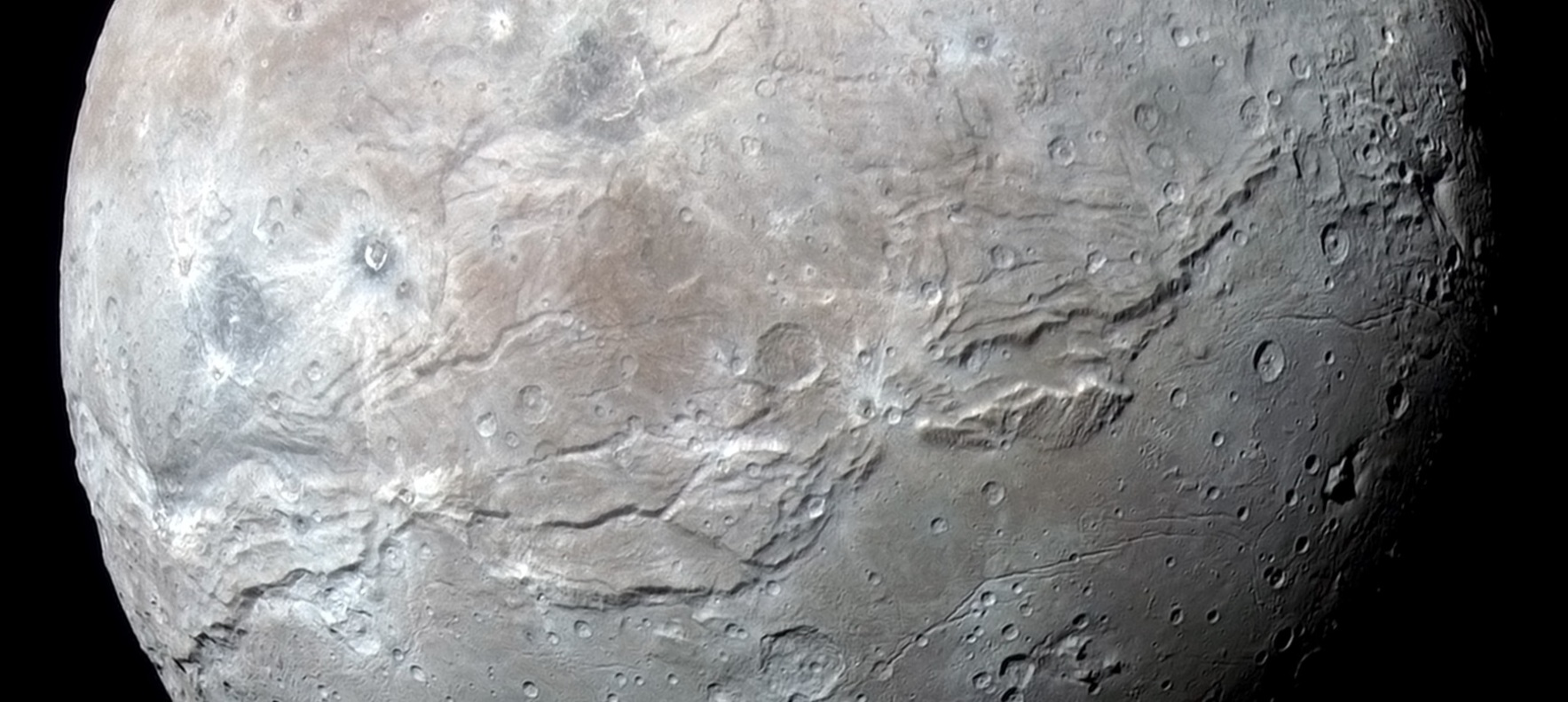 Charon's vast equatorial chasms. The most obvious ones are unofficially named Macross Chasma (on the left) and Serenity Chasma (on the right). – Image Credit: NASA/Johns Hopkins University Applied Physics Laboratory/Southwest Research Institute