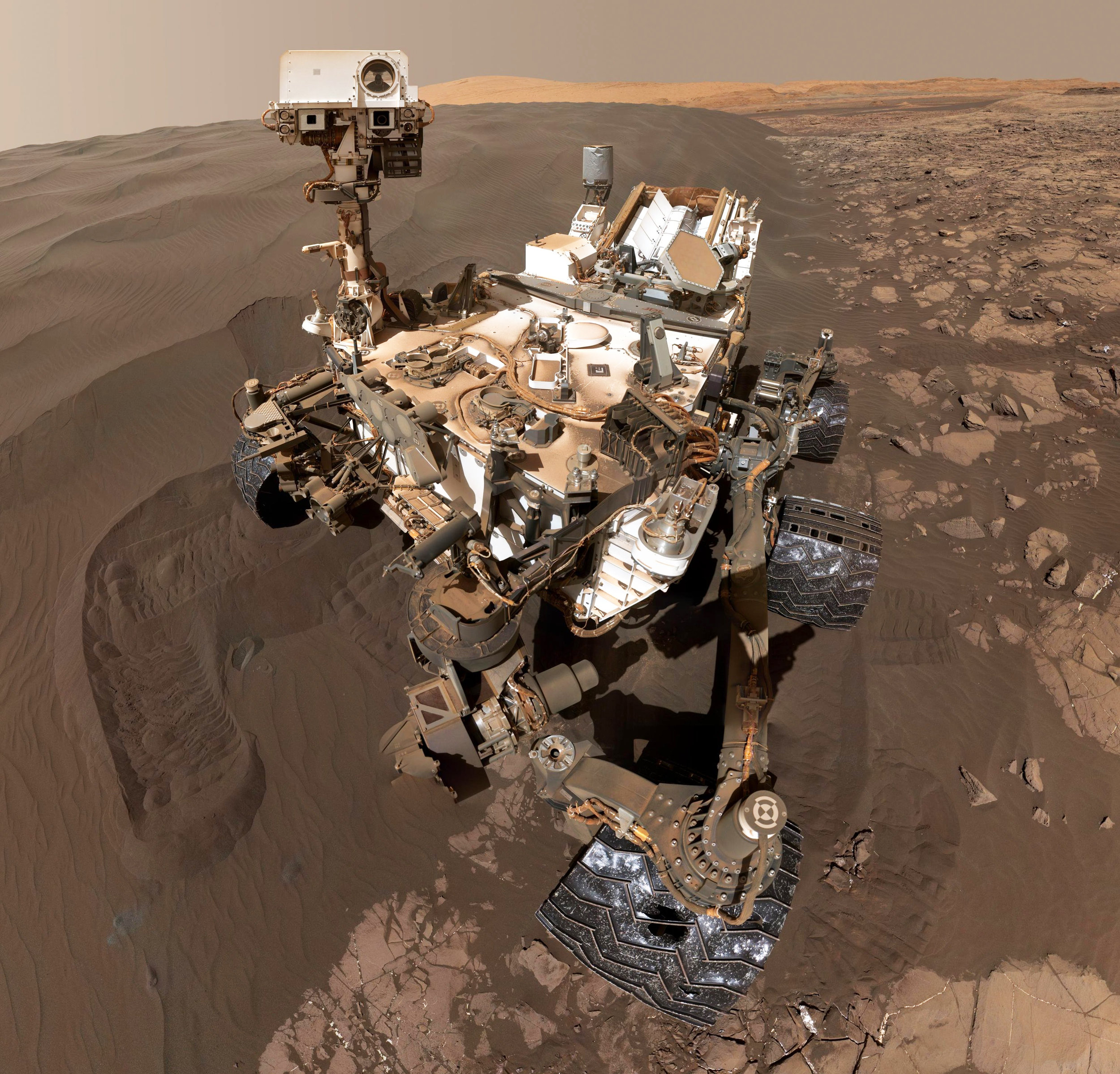 "This self-portrait of NASA's Curiosity Mars rover shows the vehicle at ""Namib Dune,"" where the rover's activities included scooping samples of regolith for analysis. ""To (utilize in-situ resource utilization resources) on a remote planet or an asteroid, the systems need to be very reliable,"" said Dr. Jim Mantovani, a Kennedy Space Center planetary scientist and granular physics researcher. When this photograph was created combining 57 images taken on Jan. 19, 2016, Curiosity was on its 1,228th day, or sol, on Mars. – Image Credits: NASA/Jet Propulsion Laboratory-Caltech"