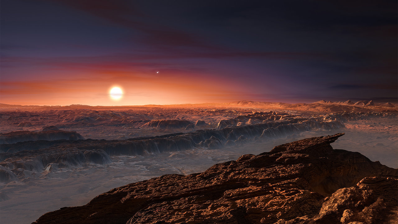 This artist's impression shows a view of the surface of the planet Proxima b orbiting the red dwarf star Proxima Centauri, the closest star to the solar system. The double star Alpha Centauri AB also appears in the image. Proxima b is a little more massive than the Earth and orbits in the habitable zone around Proxima Centauri, where the temperature is suitable for liquid water to exist on its surface. – Image Credits: ESO/M. Kornmesser