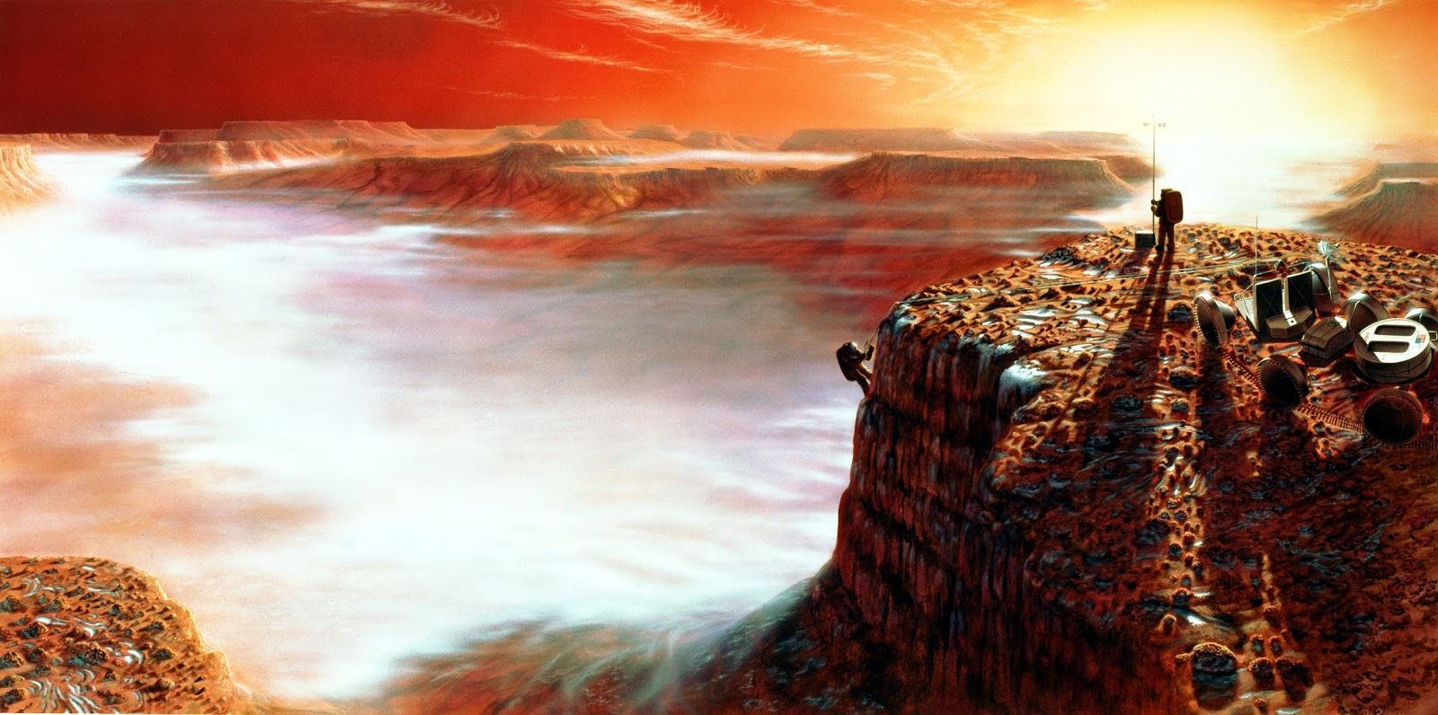 The area depicted is Noctis Labyrinthus in the Valles Marineris system of enormous canyons. The scene is just after sunrise, and on the canyon floor four miles below, early morning clouds can be seen. The frost on the surface will melt very quickly as the Sun climbs higher in the Martian sky. - Image Credit: NASA