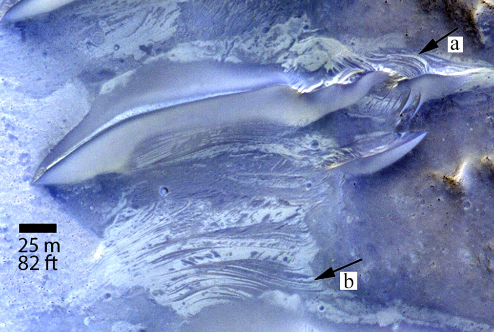 """Striations exposed on the surface between Martian sand dunes (one pictured at top) in Lucaya Crater indicate fluctuating levels of salty groundwater. At """"a"""" we see possible cross beds which are tilted layers of sand within larger layers deposited by wind or water. At b, dark and light strata are similar to that exposed in the dune at top and resemble the striations seen in the Namib Desert on Earth. The photo was taken by NASA's Mars Reconnaissance Orbiter in infrared, red and blue light. - Image Credit: NASA/JPL-Caltech"""