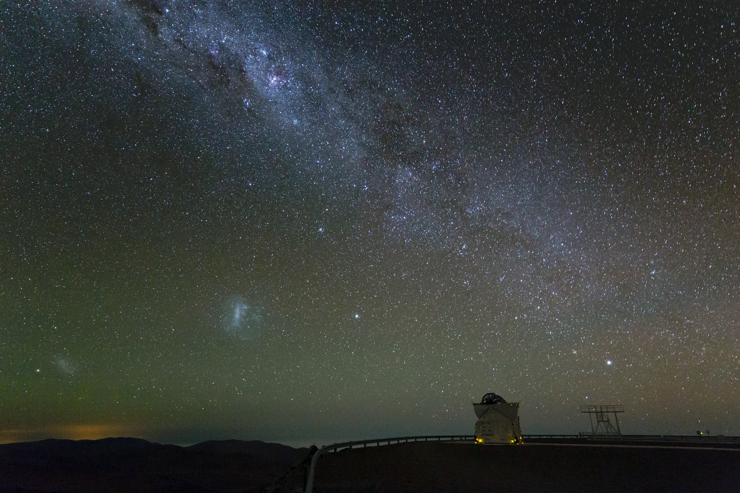 The Milky Way and its neighbouring dwarf galaxies, the Large and Small Magellanic Clouds seen in the lower left. - Image Credit: ESO/C. Malin