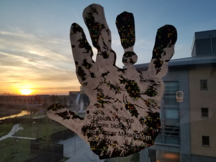 Artistic illustration of an epigenomic handprint capturing regulation of a person beyond changes in DNA. In background research campus with art statue 'New Beginnings,' symbolizing hope for cure. - Image Credit: Systems Biology and Cancer Metabolism Laboratory, Fabian V. Filipp