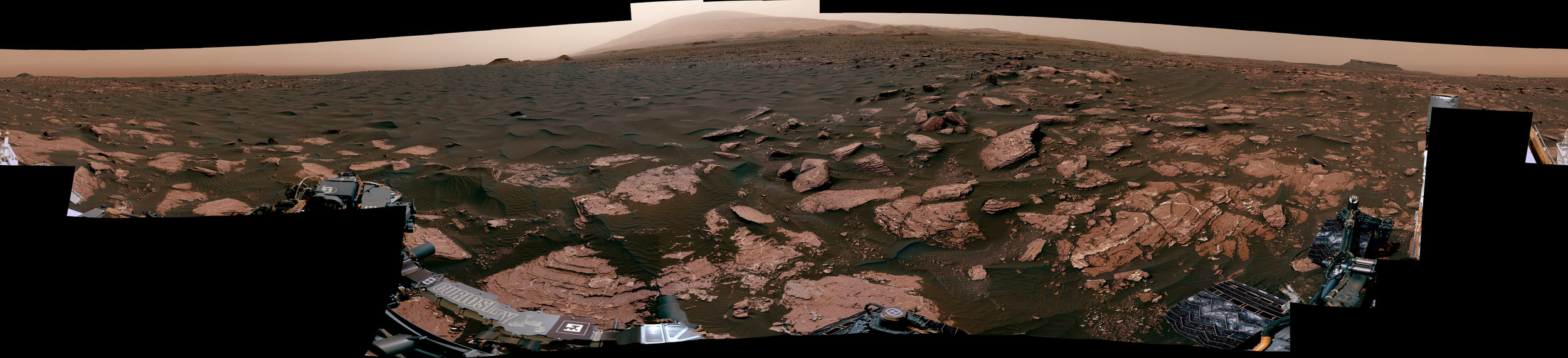 This 360-degree scene from the Mastcam on NASA's Curiosity Mars rover includes part of a linear-shaped dune the rover examined in early 2017 for comparison with what it found previously at crescent-shaped dunes. The view shows the dark, rippled surface of the active dune, near sedimentary bedrock. - Image Credits: NASA/JPL-Caltech/MSSS