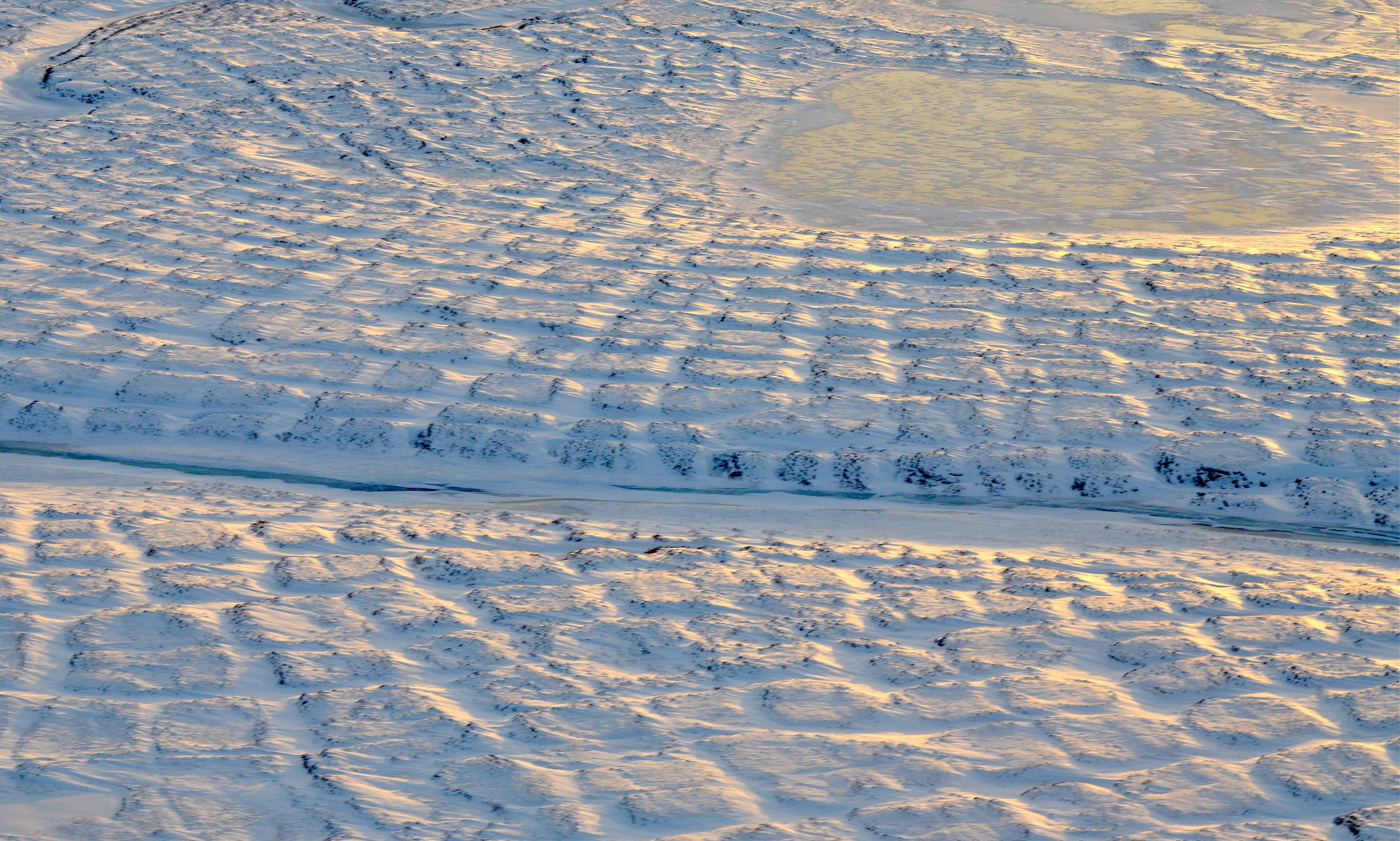 Winter sun setting over the tundra polygons in northern Alaska in November 2015. As winter sets in and snow settles, the soils take time to freeze completely and continue to emit carbon dioxide long into the new year. - Image Credits: NASA/JPL-Caltech/Charles Miller
