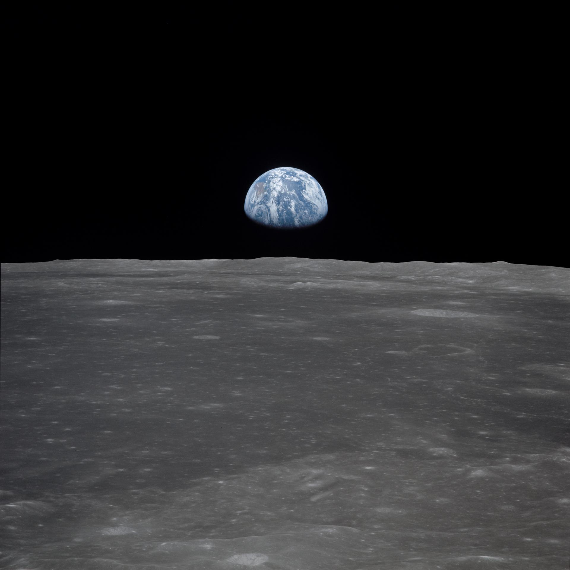 A view from the Apollo 11 spacecraft, showing the Earth rising above the moon's horizon (July 1969). - Image Credit: NASA