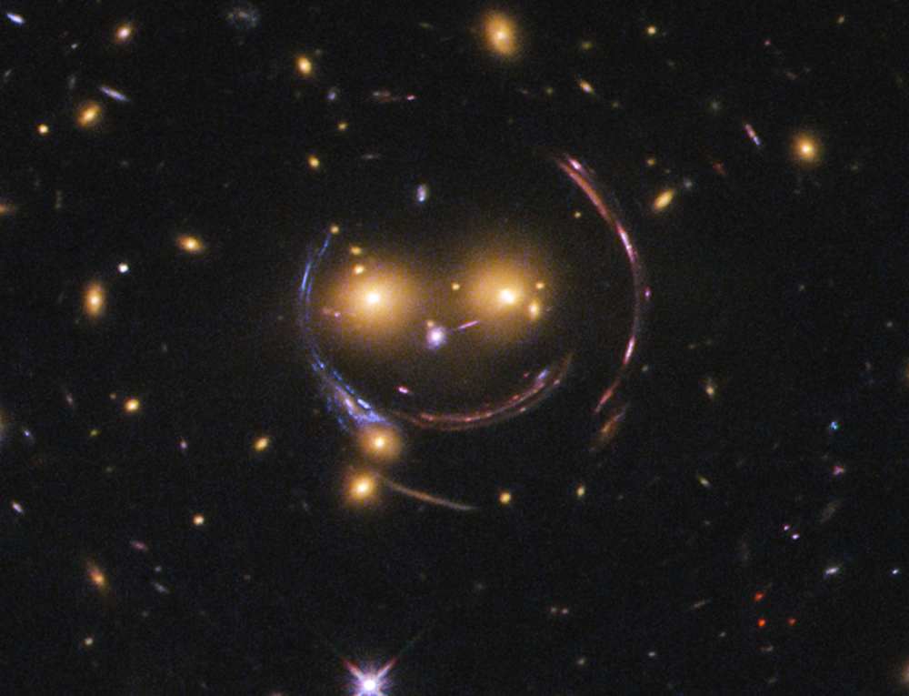 Dark matter is likely to be causing the arcs seen around the central galaxies in this image, making a smiling face.- Image Credit: NASA/ESA,  CC BY-SA