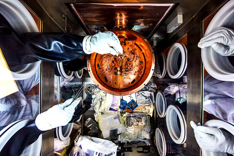 Researchers work on the delicate wiring of a cryostat, which chills the detectors that are the heart of the MAJORANA DEMONSTRATOR. - Image Credit: Matthew Kapust/Sanford Underground Research Facility via U. Washington