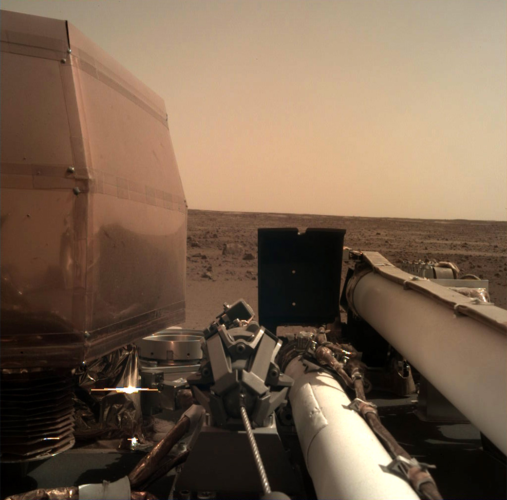 The Instrument Deployment Camera (IDC), located on the robotic arm of NASA's InSight lander, took this picture of the Martian surface on Nov. 26, 2018, the same day the spacecraft touched down on the Red Planet. The camera's transparent dust cover is still on in this image, to prevent particulates kicked up during landing from settling on the camera's lens. This image was relayed from InSight to Earth via NASA's Odyssey spacecraft, currently orbiting Mars. - Image Credits: NASA/JPL-Caltech