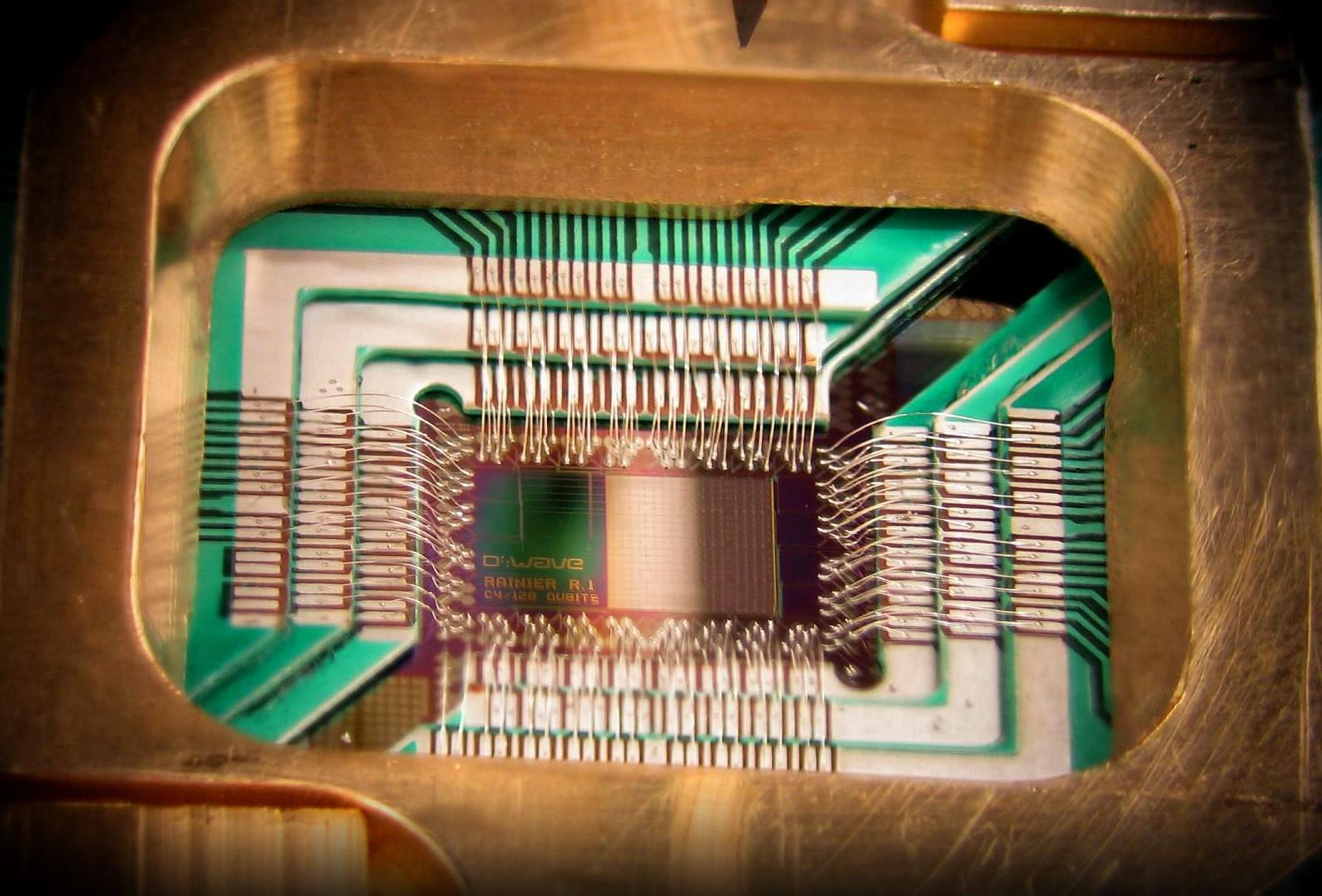 Photograph of a chip constructed by D-Wave Systems Inc. designed to operate as a 128-qubit superconducting adiabatic quantum optimization processor, mounted in a sample holder. Image Credit:  D-Wave Systems, Inc. via Wikimedia Commons