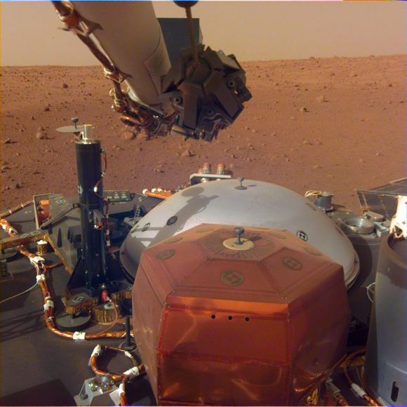 This image was taken by the InSight Lander's Instrument Deployment Camera mounted on the lander's robotic arm. The stowed grapple on the end of the arm is folded in, but it will unfold and be used to deploy the lander's science instrument. The copper-colored hexagonal object is the protective cover for the seismometer, and the grey dome behind it is a wind and thermal shield, which will be placed over the seismometer after its deployed. The black cyliner on the left is the heat probe, which will drill up to 5 meters into the Martian surface. - Image Credit: NASA/JPL-Caltec