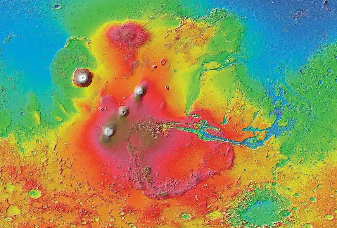 A colorized image of the surface of Mars taken by the Mars Reconnaissance Orbiter. The line of three volcanoes is the Tharsis Montes, with Olympus Mons to the northwest. Valles Marineris is to the east. - Image Credit: NASA/JPL-Caltech/ Arizona State University