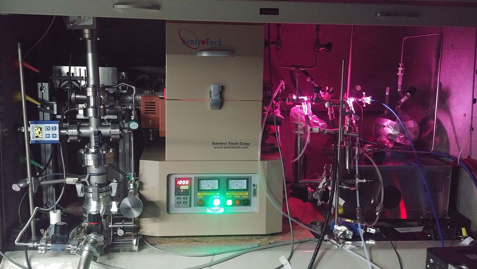 "JPL scientists used the ""oven"" (center) to heat a mixture of hydrogen and carbon monoxide and subject it to UV radiation, generated by a hydrogen gas discharge lamp. The lamp radiates both visible light (the pink glow) and UV light, which enters the gas container inside the oven via a window on the right side. - Image Credits: NASA/JPL-Caltech"