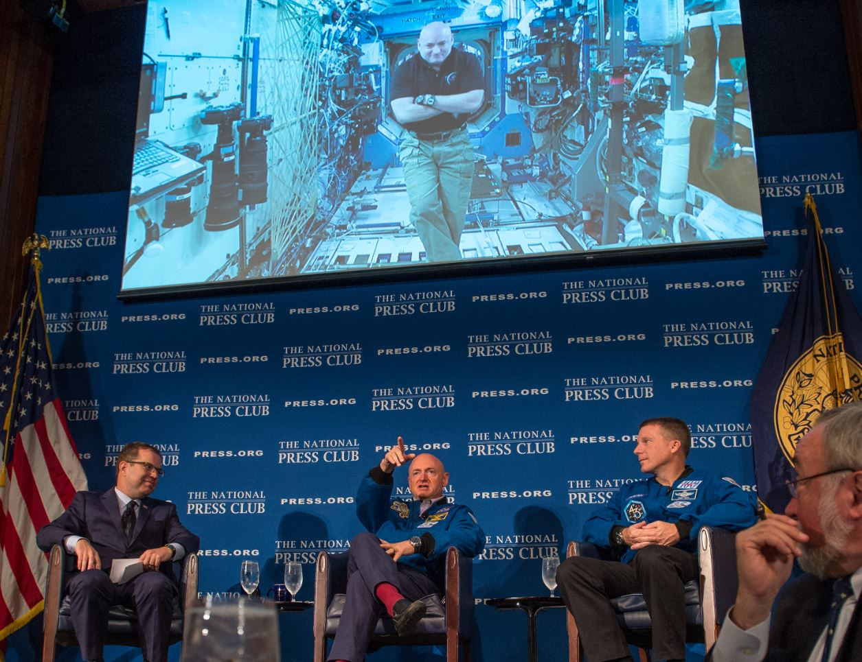 One day before astronaut Scott Kelly reaches the six-month mark in space, he talks live from onboard the ISS with John Hughs, left, his twin brother Mark Kelly and Astronaut Terry Virts, right. - Image Credit:  NASA/Bill Ingalls