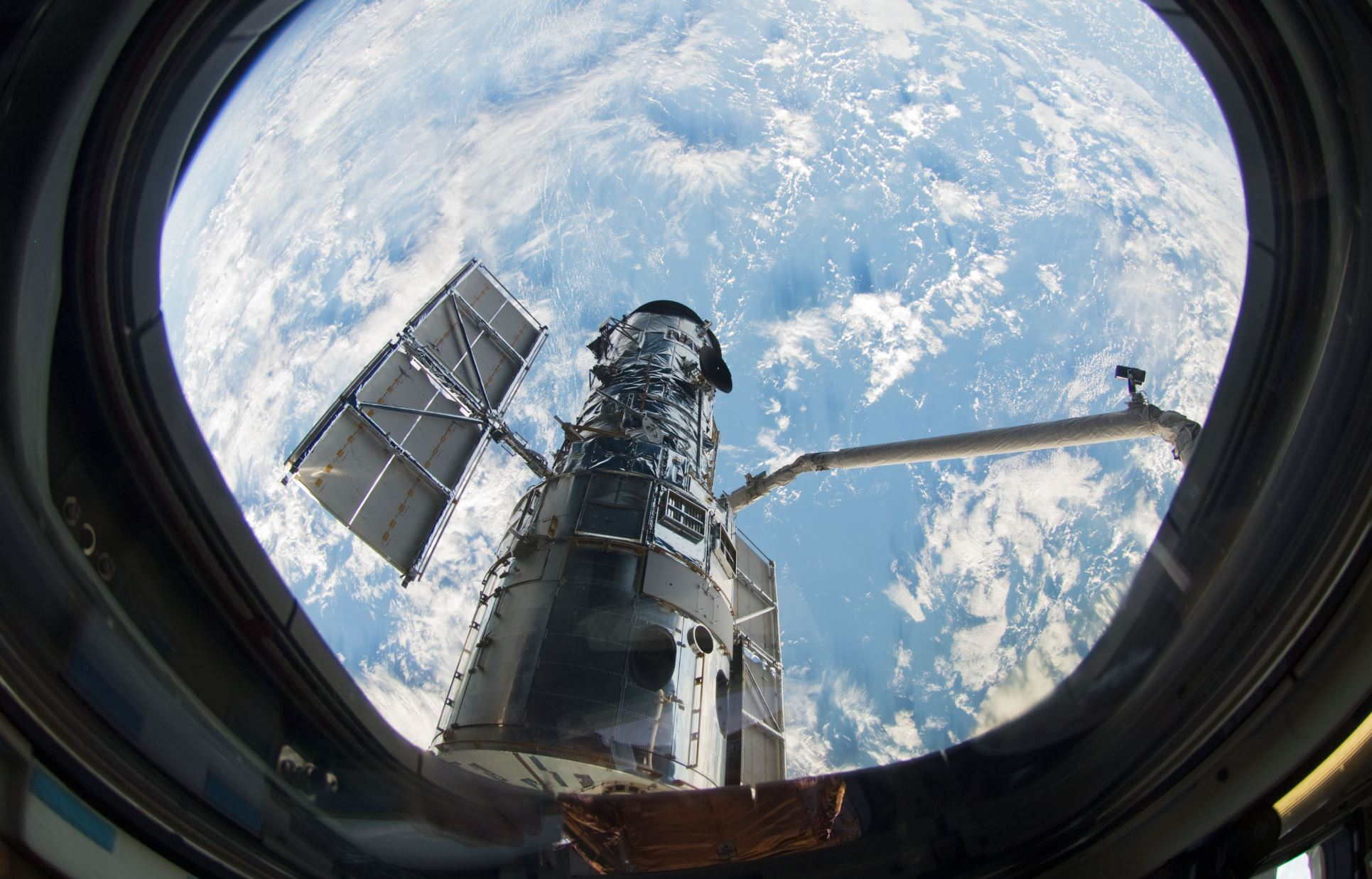 A window on the space shuttle Atlantis frames Hubble as astronaut Megan McArthur uses the shuttle's robot arm to grab the telescope in preparation for the final servicing mission. From its perch 340 miles above Earth, the famed space telescope has tracked celestial objects across the universe. - Image Credit: NASA
