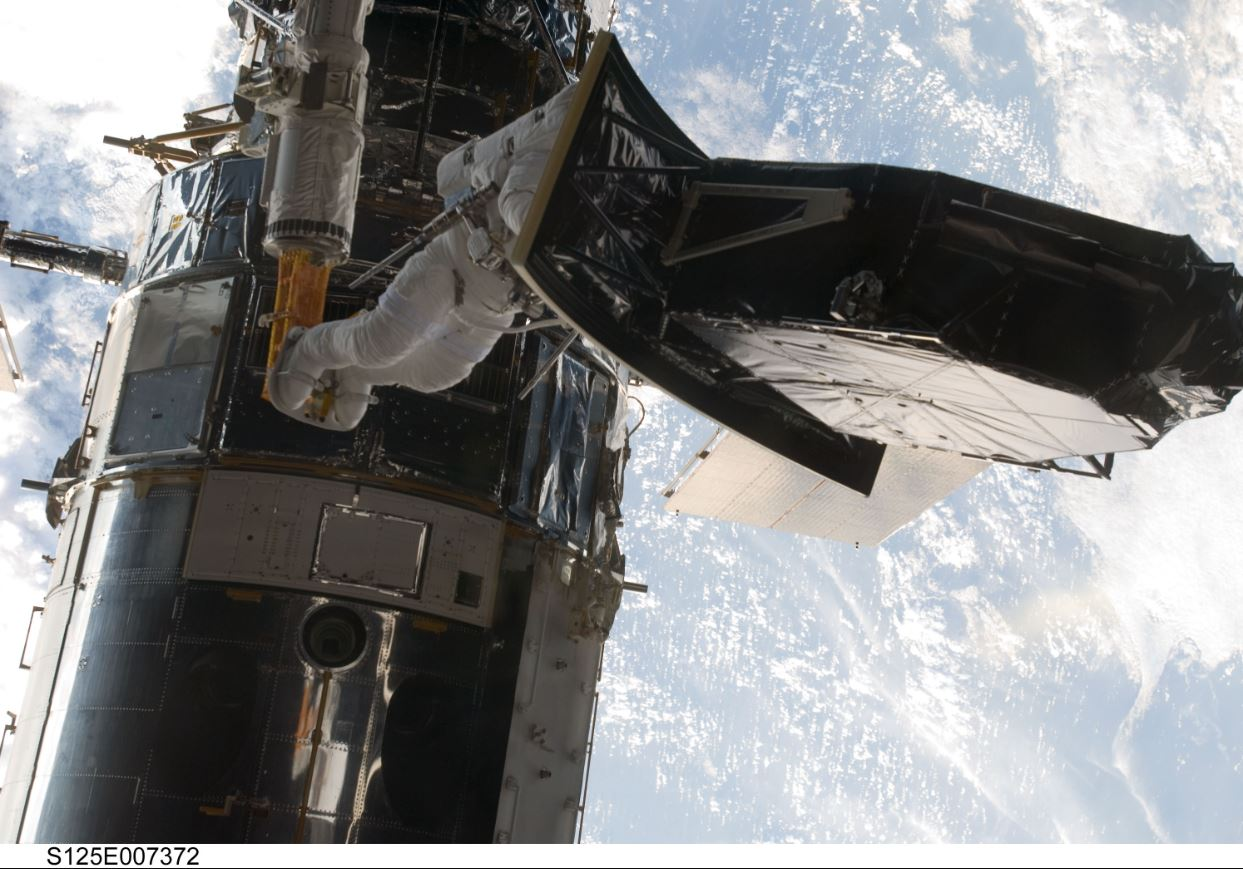 Astronaut Andrew Feustel wrangles the Wild Field and Planetary Camera 2, which he, along with John Grunsfeld, replaced with the new Wide Field Camera 3 (WFC3) during the first spacewalk of the servicing mission on May 14, 2009. Since its installation, the WFC3 has imaged a variety of targets from distant galaxies to moons circling other planets in our solar system. - Image Credit: NASA