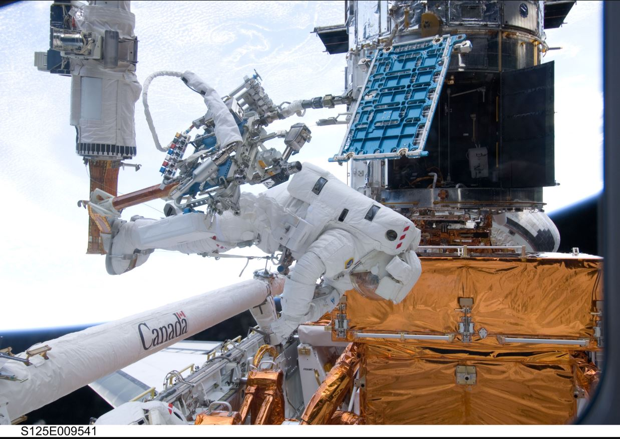 During the mission's fourth spacewalk, Michael Good and Michael Massimino faced a curious challenge: a stripped screw delayed the removal of a handrail (pictured inside the telescope to the upper right of Good's helmet in this photo) on the outside of the Space Telescope Imaging Spectrograph (STIS). After nearly four hours of troubleshooting, Good, Massimino, the rest of the crew and a team back on Earth found a way to remove the handrail and continue the mission. - Image Credit: NASA