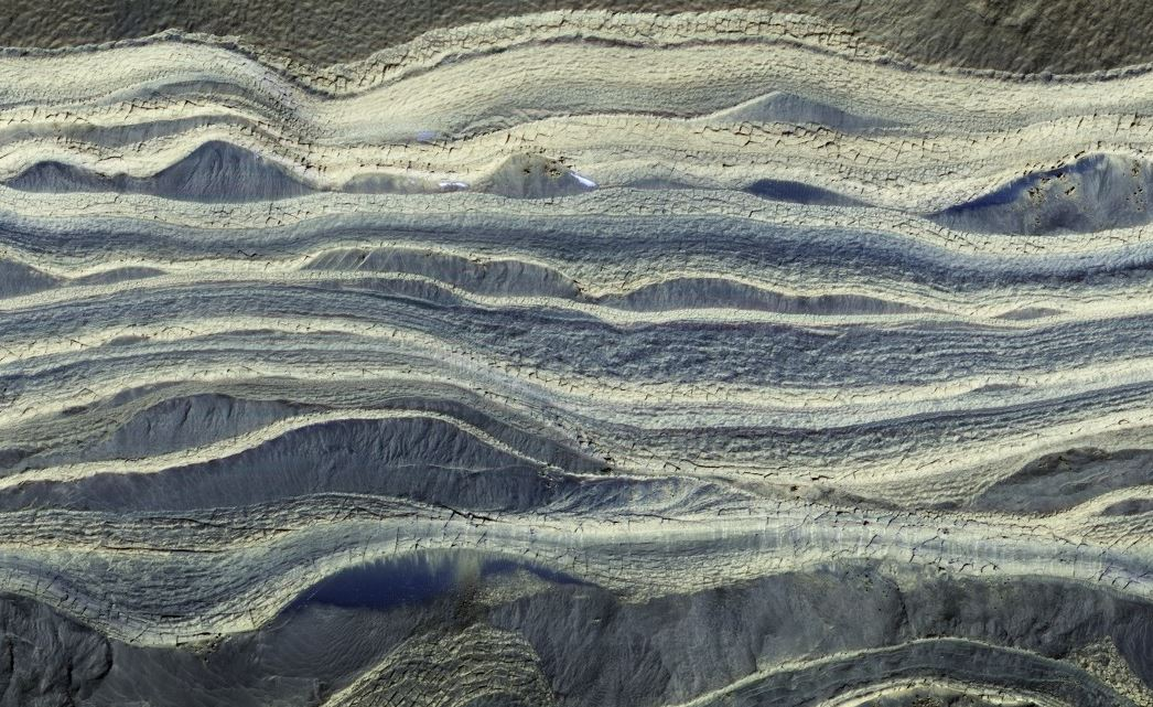A composite image showing alternating layers of ice and sand in an area where they are exposed on the surface of Mars, taken with the MRO's HiRISE camera. - Image Credit: NASA/JPL/University of Arizona