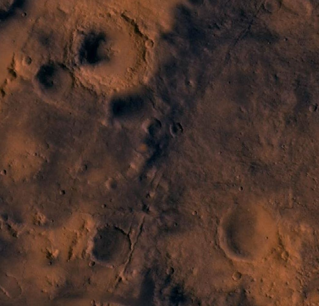 In this image from the Viking orbiter, Jezero Crater is in the lower right. Faintly visible is the overflow water channel on the right of the crater. Image Credit: By NASA – en:Image:Syrtis Major MC-13.jpg – Cropped – Original image produced using images from the Viking Orbiter 1 Visual Imaging Subsystem – Camera A.,  - Image Credit:  NASA via Wikimedia Commons