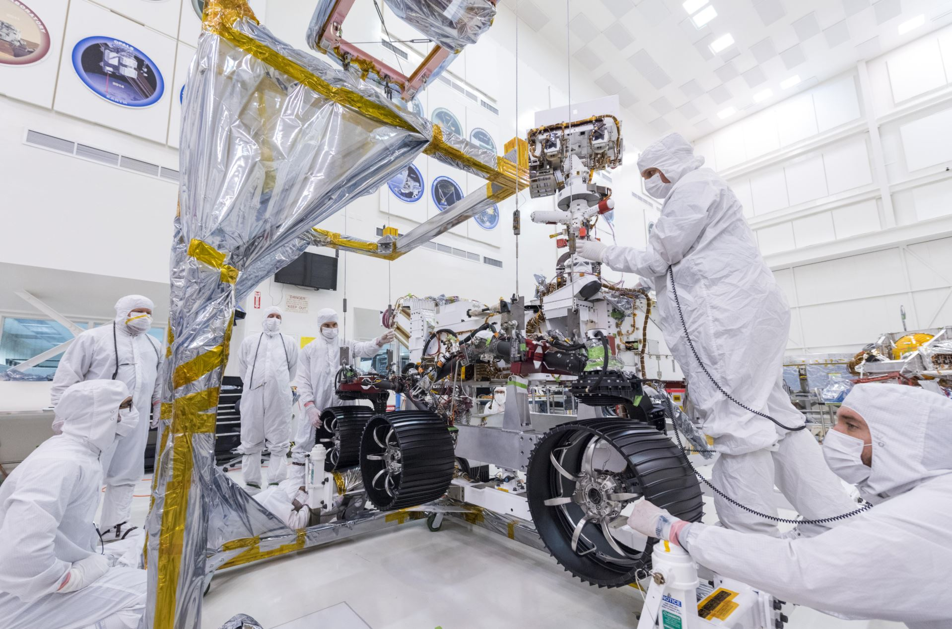 In this image, taken on June 13, 2019, engineers at JPL install the starboard legs and wheels - otherwise known as the mobility suspension - on the Mars 2020 rover. Credit: NASA/JPL-Caltech - Image credit: NASA/JPL-Caltech