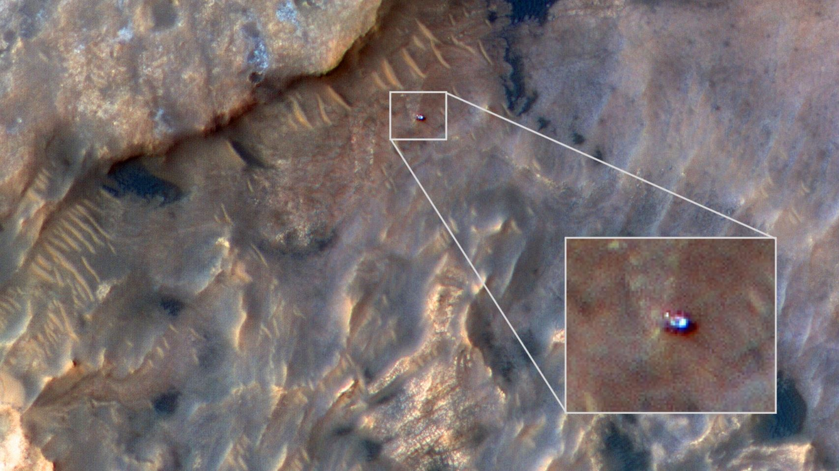 NASA's Curiosity Mars rover can be seen in this image taken from space on May 31, 2019, by the HiRISE camera aboard the Mars Reconnaissance Orbiter. In the image, Curiosity appears as a bluish speck. - Image Credits: NASA/JPL-Caltech