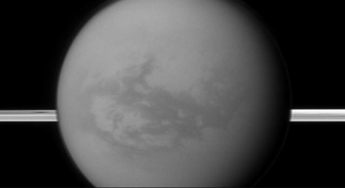 Saturn's rings lie in the distance as the Cassini spacecraft looks toward Titan and its dark region called Shangri-La, east of the landing site of the Huygens Probe. - Image Credits: NASA/JPL-Caltech/Space Science Institute