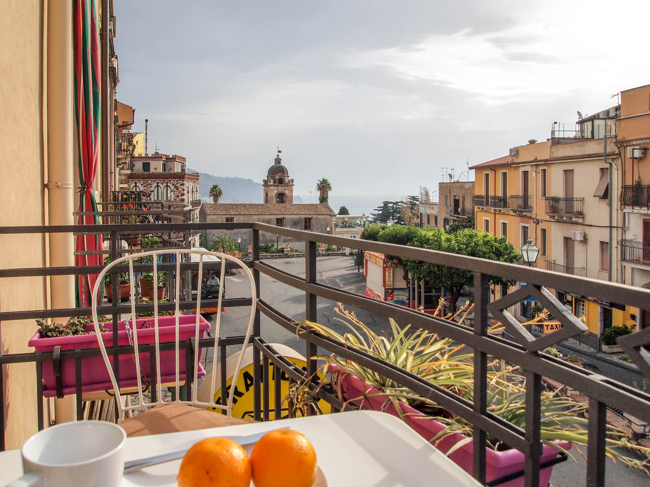 Our nice little balcony overlooking the main street and the sea! Breakfast on the table!