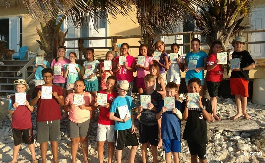 School children at the Little Cayman Research Center with their copies of 'A Parrotfish's Tale' CCMI Ed. Photo credit: CCMI 2016.