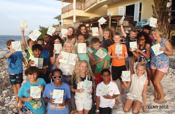Visiting students holding the CCMI edition of ''A Parrotfish's Tale'' at the Central Caribbean Marine Institute (CCM) on Little Cayman, Cayman Islands.