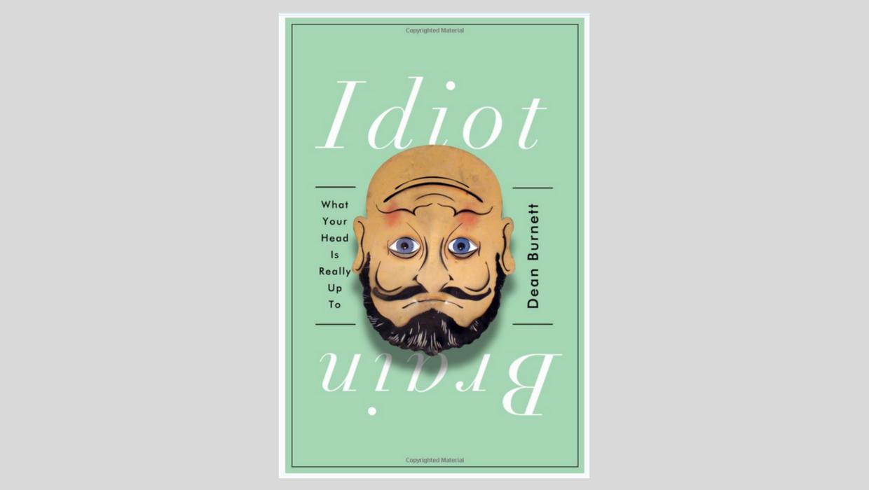 (Descrição da imagem: Capa do livro Idiot Brain. A capa mostra uma imagem de ilusão de ótica onde o desenho do rosto de um homem parece estar tanto de cabeça para cima como de cabeça para baixo)