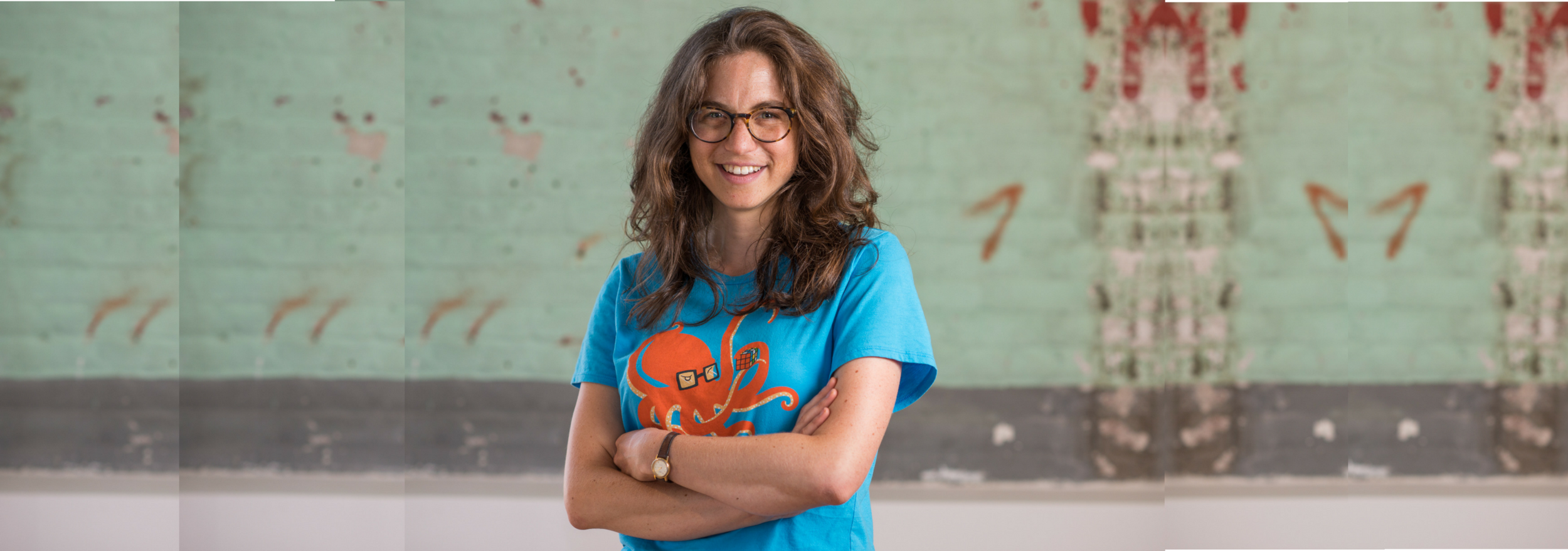 (Descrição da imagem: A reportér Wendy Zuckerman posa de braços cruzados em frente a um muro de tijolos azul claro. Ela está sorrindo e usando uma camisa com um desenho de um polvo de óculos)