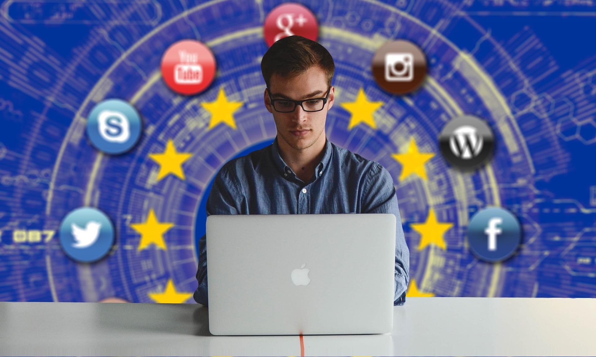 (Descrição da imagem: Homem jovem usa o computador. Atrás dele, o fundo da imagem mostra os ícones de diferentes redes sociais como Twitter, Facebook e YouTube)