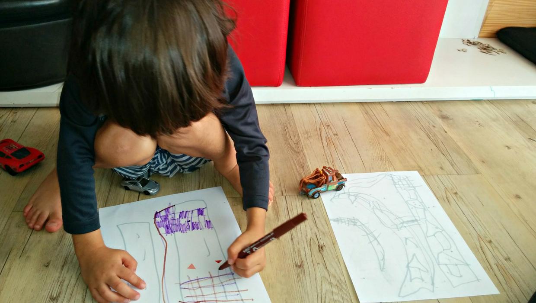 Meu sobrinho super sabido.  (Descrição da imagem: Garoto de 4 anos anos está acocorado no chão desenhando em um papel com uma caneta)