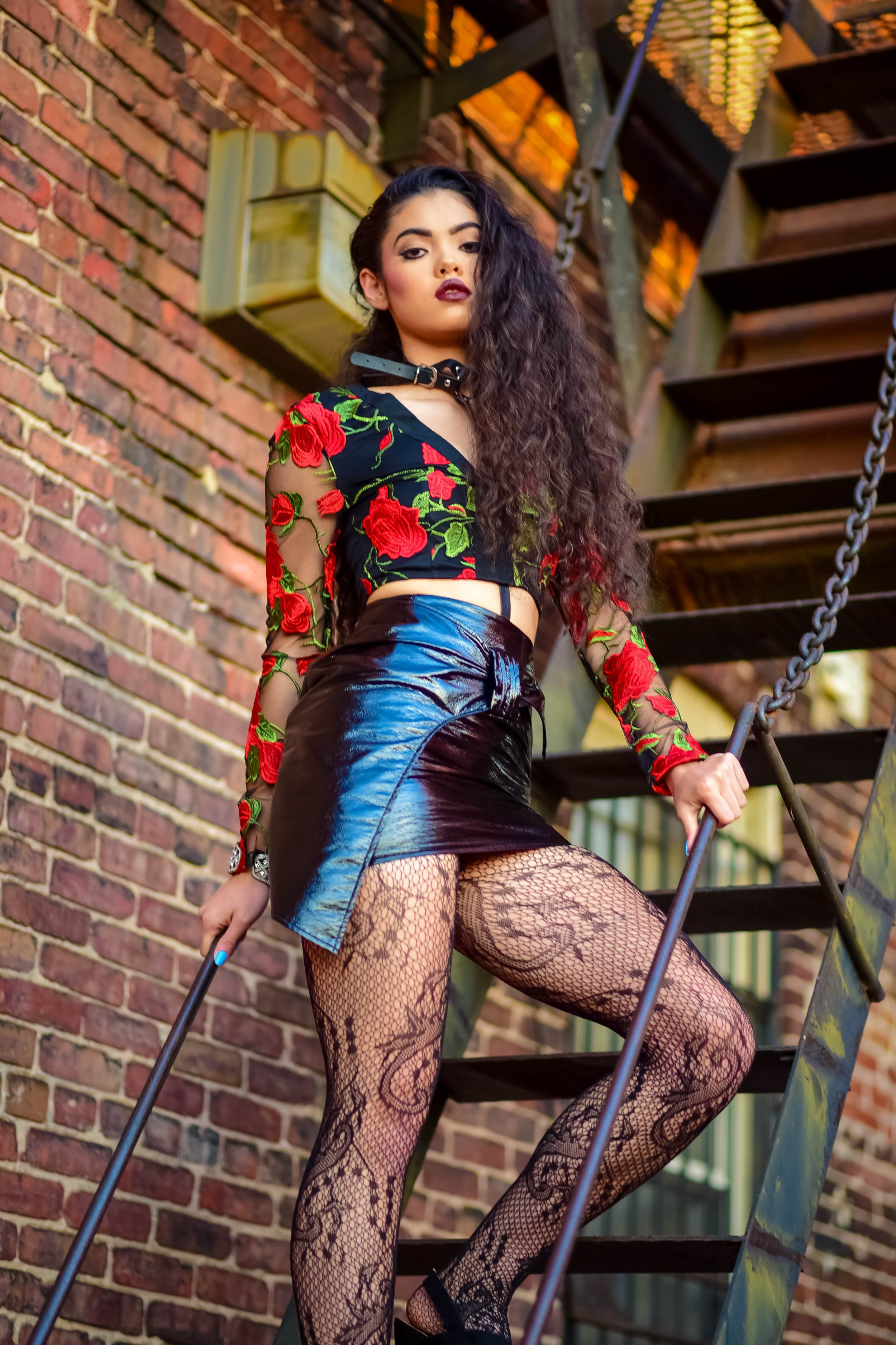 Get the Look:   Amanda wears a  black floral embroidered top ,  black faux leather tie belted mini ,  lace tights , harness choker.