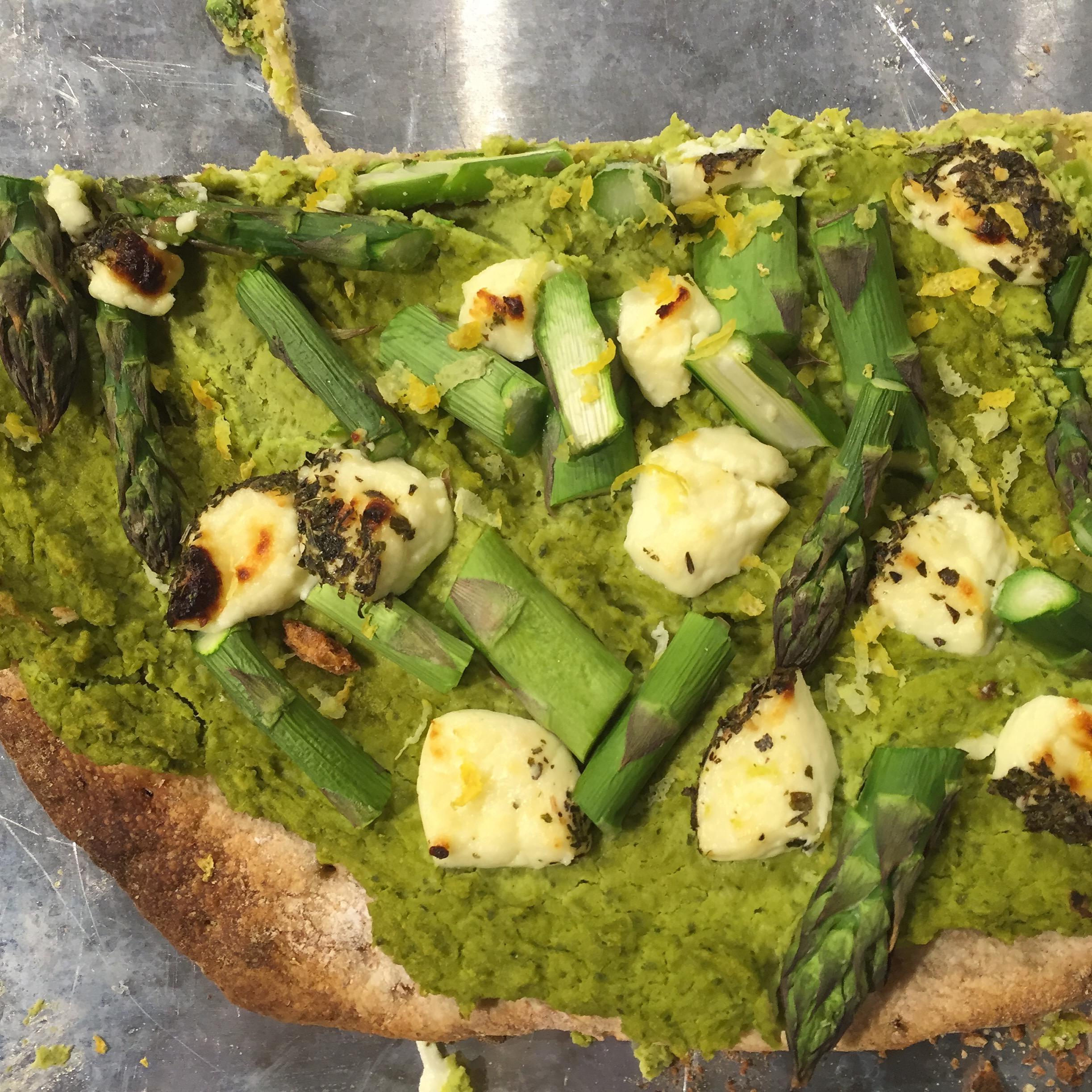 Pizza with pea-cilantro hummus, asparagus, herbed chevre and lemon zest